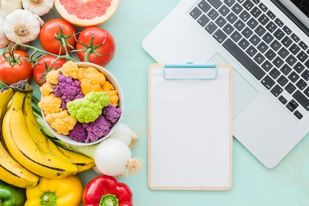 Aliments santé avec presse-papiers vierge et ordinateur portable sur le bureau Photo gratuit