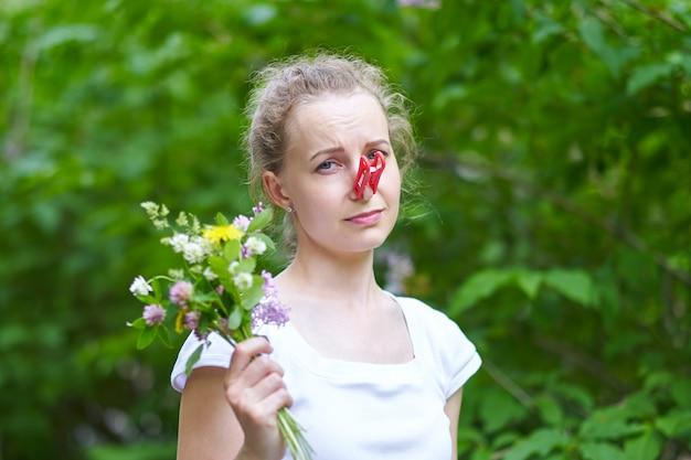 Allergie. Une Femme Se Serra Le Nez Avec Une Pince à Linge, Pour Ne Pas éternuer Du Pollen Des Fleurs Photo Premium