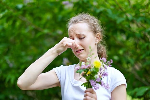 Allergie. Femme Serrant Le Nez Avec La Main, Pour Ne Pas éternuer Du Pollen Des Fleurs Photo Premium