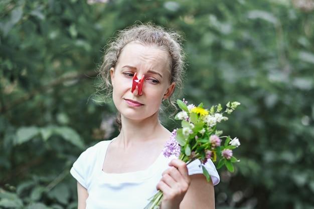 Allergie. Femme Serrant Le Nez Avec Une Pince à Linge, Pour Ne Pas éternuer Du Pollen Des Fleurs Photo Premium