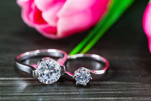 Alliances diamant avec fleur de tulipe sur fond noir Photo Premium