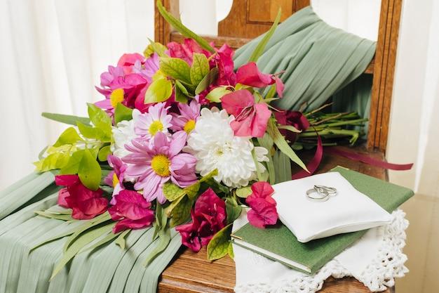 Alliances sur l'oreiller sur un livre près du bouquet de fleurs et robe de mariée sur une chaise Photo gratuit