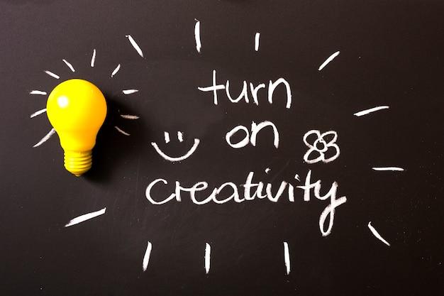 Allumez le texte de créativité écrit à la craie sur le tableau noir avec une ampoule jaune Photo gratuit