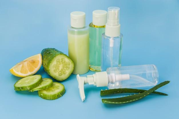 Aloe vera frais; tranches de citron et de concombre vaporisateurs sur fond bleu Photo gratuit