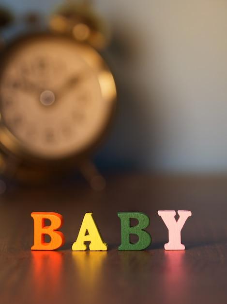 Alphabet bébé sur table en bois et réveil vintage Photo Premium