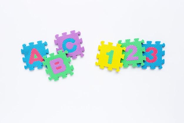 Alphabet avec numéro de puzzle sur blanc. Photo Premium