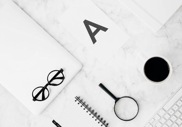 Alphabet a sur papier; loupes; journal intime; tasse à café; tablette numérique; clavier sur toile de fond texturée Photo gratuit