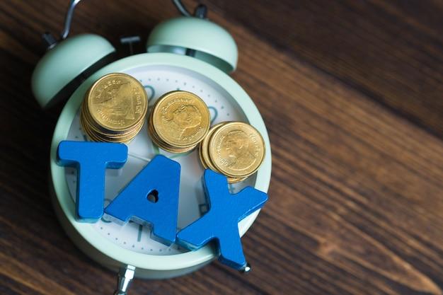 Alphabet tax avec pile de pièces de monnaie et réveil vintage Photo Premium
