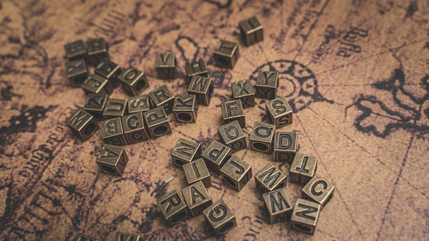 Alphabets en bronze vintages sur carte du vieux monde Photo Premium