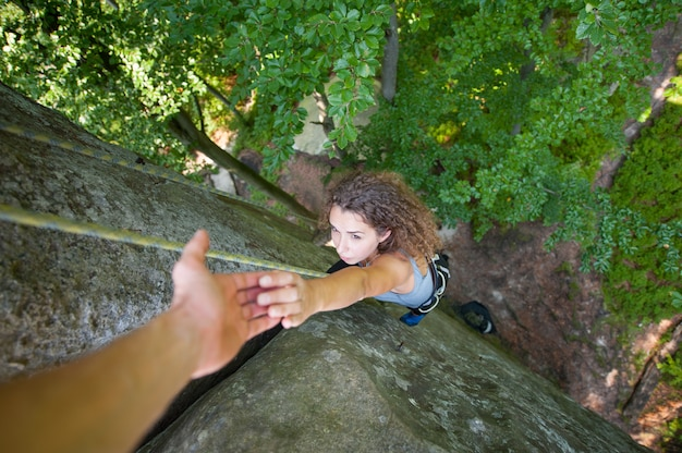 Un alpiniste aide une femme à atteindre le sommet d'une montagne Photo Premium