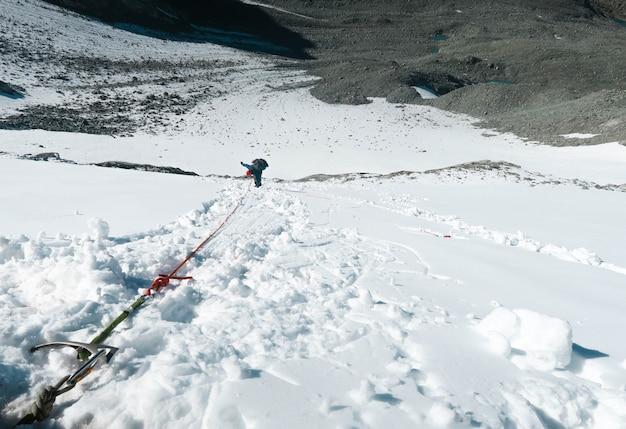 Alpiniste descendant le mur vertical. matériel d'escalade. col enneigé Photo Premium