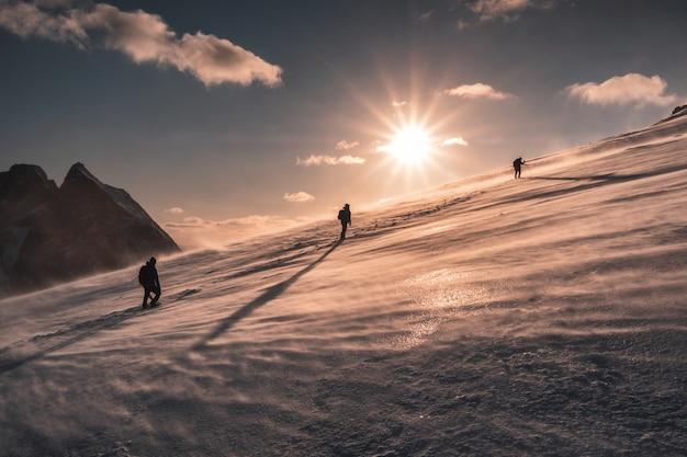 Alpinistes escalade dans la tempête de neige sur la colline enneigée au coucher du soleil Photo Premium