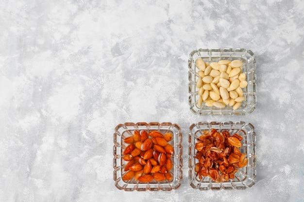 Amandes entières pelées (blanchies) et non blanchies dans des bols de verre sur du béton gris Photo gratuit