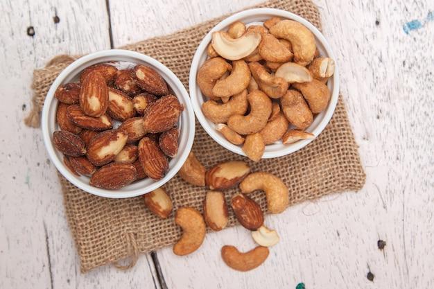 Amandes et noix de cajou dans la tasse blanche et mettre un sac de toile sur le plancher de bois Photo Premium