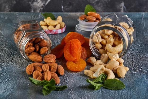 Des amandes de noix de cajou se répandent dans des boîtes transparentes, entre des abricots secs Photo Premium