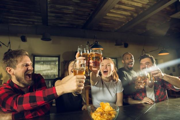Les Amateurs De Sport Applaudissent Au Bar, Au Pub Et Boivent De La Bière Pendant Le Championnat Et La Compétition Photo gratuit