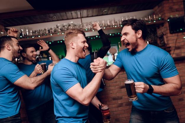 Les amateurs de sport buvant des ours applaudir au bar des sports Photo Premium