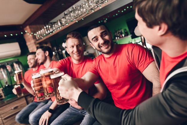 Les amateurs de sport célèbrent et encouragent boire de la bière Photo Premium