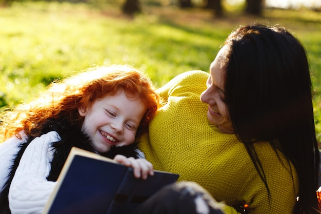 Ambiance d'automne, portrait de famille. charmante maman et sa fille aux cheveux roux s'amusent assises sur le tombé Photo gratuit