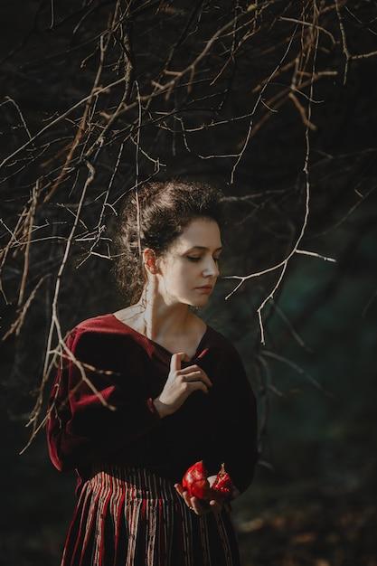 Ambiance d'automne. style gothique. femme brune en tissu rouge foncé Photo gratuit