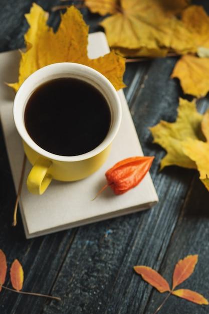 Ambiance de confort d'automne. tasse de café, livre et feuilles d'automne lumineux avec fond Photo Premium