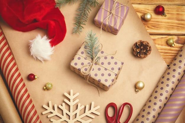 Ambiance festive de noël. plat-lay de décorations, rubans, papier cadeau, cadeau emballé sur fond en bois Photo Premium