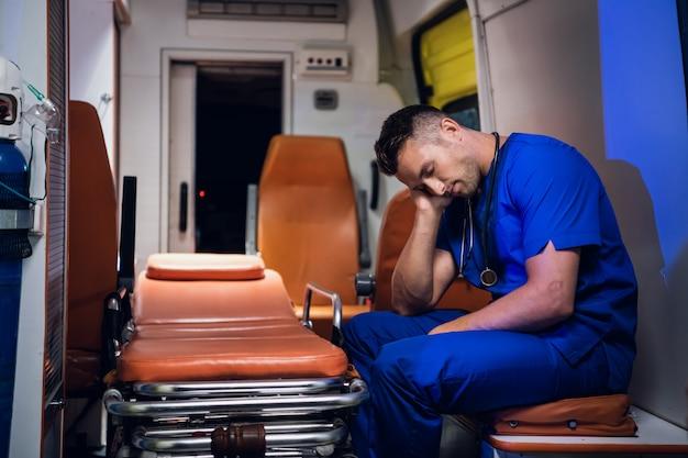 Ambulancier épuisé Dormant Dans Une Voiture D'ambulance Photo Premium