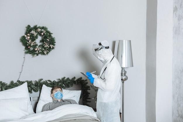 Un Ambulancier Vêtu D'une Combinaison De Protection Epi Hazmat Examine Un Patient Malade Atteint Du Coronavirus Covid-19 Avant Le Nouvel An Et Noël Photo Premium