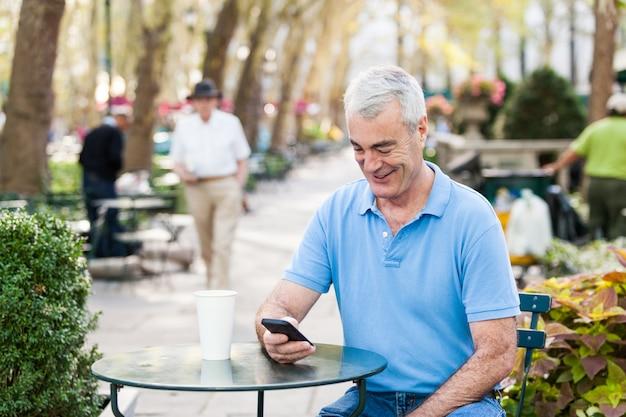 Américain senior homme avec téléphone portable au parc Photo Premium