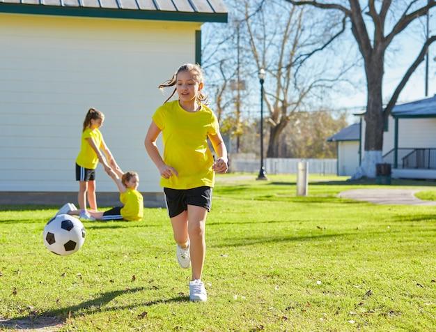 Ami filles adolescentes jouant au football football dans un parc Photo Premium