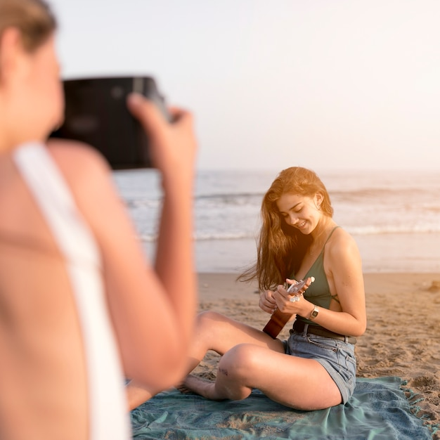 Ami prenant selfie de fille jouant du ukulélé à la plage Photo gratuit