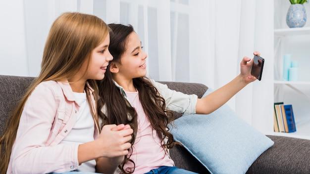 Amies assis sur le canapé prenant selfie sur téléphone intelligent Photo gratuit