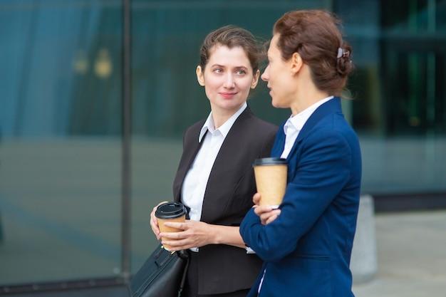 Amies De Bureau Positives Avec Des Tasses à Café à Emporter Marchant Ensemble à L'extérieur, Parlant, Discutant D'un Projet Ou Discutant. Coup Moyen. Concept De Pause De Travail Photo gratuit