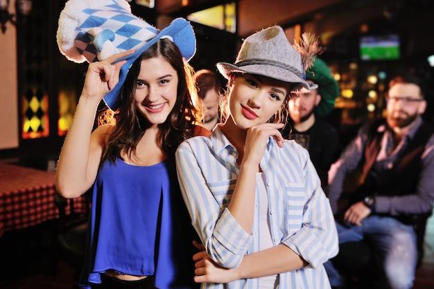 Amies en chapeaux bavarois souriant au fond du bar lors de la célébration de la fête de la bière Photo Premium