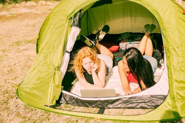 Amies dans la tente à l'aide d'un ordinateur portable Photo gratuit