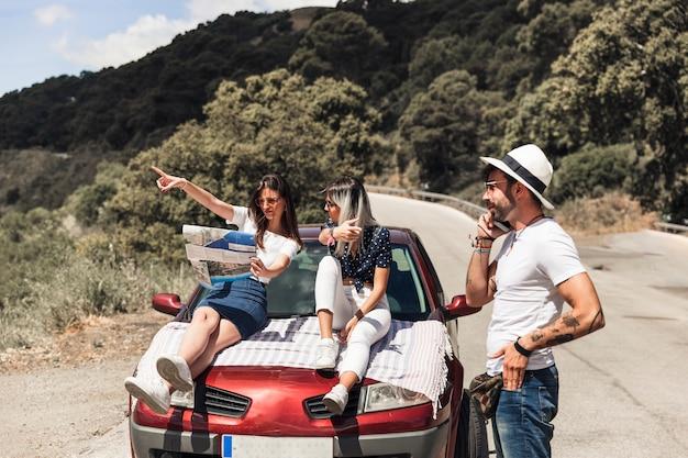 Amies discutant de la direction sur la carte en face de l'homme parlant au téléphone mobile Photo gratuit
