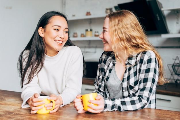 Amies discutant avec des tasses de thé Photo gratuit