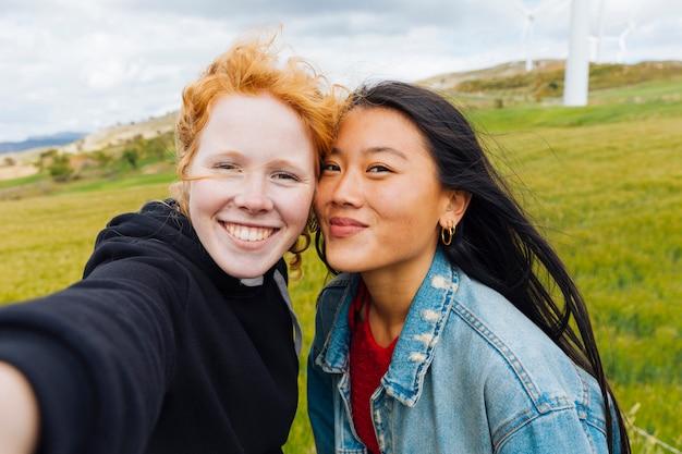 Amies prenant selfie sur le parc éolien Photo gratuit