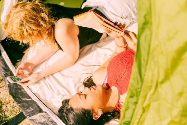 Amies se détendre en position couchée dans la tente Photo gratuit
