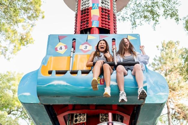 Amies Smiley S'amusant Dans Le Parc D'attractions Photo gratuit