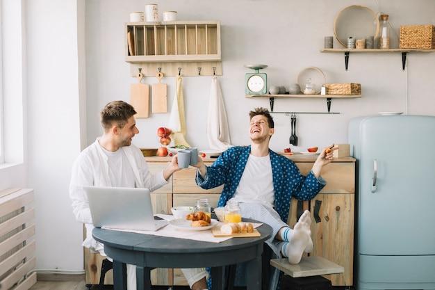 Amis, acclamation, tasse café, à, nourriture fraîche, et, ordinateur portable, sur, table Photo gratuit