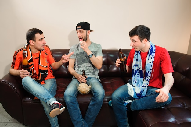 Amis applaudissant et buvant de l'alcool tout en regardant un match de football Photo Premium