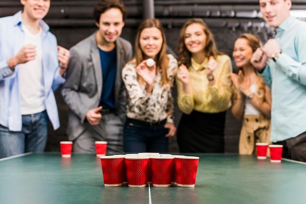 Amis appréciant le jeu de bière-pong sur la table dans le bar Photo gratuit
