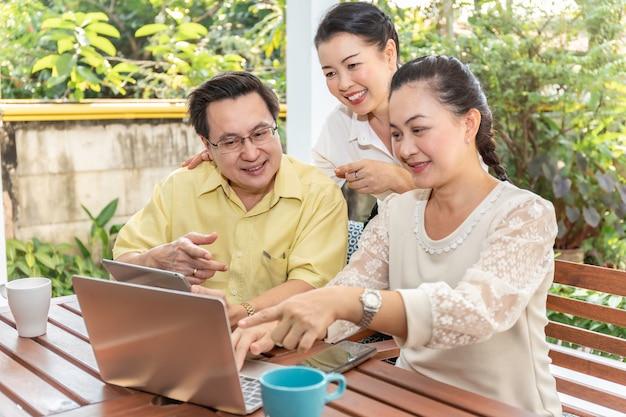 Amis Asiatiques âgés Utilisant Des Ordinateurs Portables Et Des Tablettes Dans Une Maison De Soins Infirmiers. Photo Premium