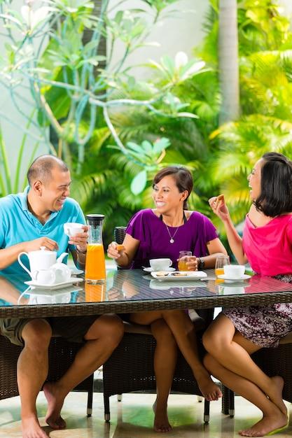Amis asiatiques ayant un café sur le porche de la maison Photo Premium