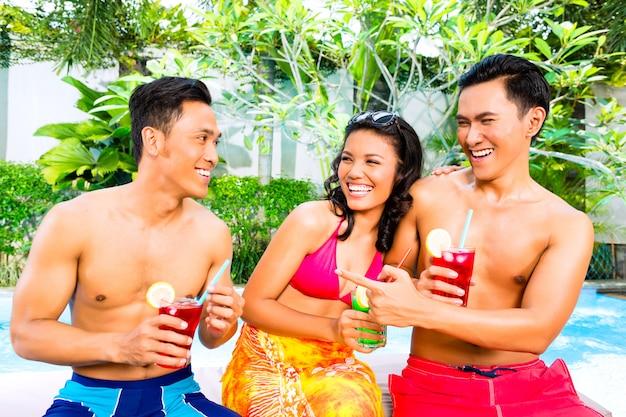 Amis asiatiques buvant des cocktails au bord de la piscine Photo Premium