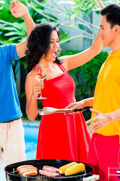 Amis asiatiques célébrant un barbecue à la piscine Photo Premium