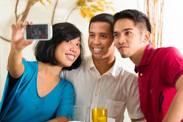 Amis asiatiques prenant des photos avec un téléphone mobile Photo Premium