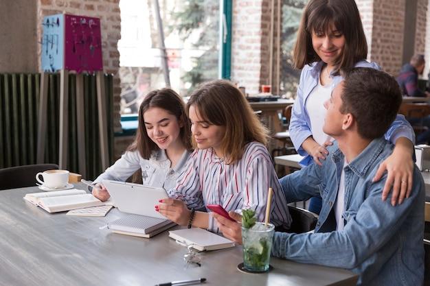 Amis assis au café avec tablette Photo gratuit