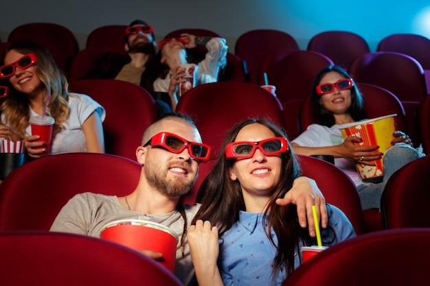 Des amis assis au cinéma regardent un film en train de manger du maïs soufflé et de l'eau potable. Photo Premium